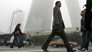 Pessoas andam por rua de Pequim tomada de neblina. Foto: AP