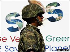 Miembro del ejército delante de la pancarta SOS