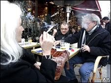 Gente fumando frente a un café.