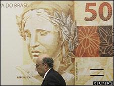 El presidente del Banco Central de Brasil, Henrique Meirelles, pasa por delante de un billete gigante
