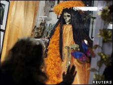 Mujer ante el altar de la Santa Muerte