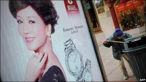 上海街头巨型广告牌边一老人在淘垃圾