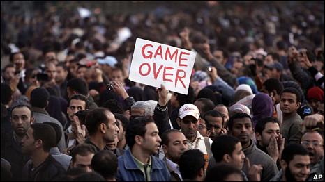"""埃及开罗解放广场上一名示威者举起""""游戏结束""""的抗议标语(29/1/2011)"""