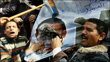 Người biểu tình vẽ bẩn và đập giầy vào áp phích có hình ông Mubarak