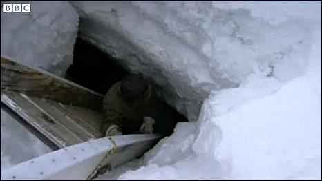 Esquimó desce a caverna de gelo formada no mar Ártico