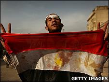 埃及开罗解放广场上一名反政府示威者在展示一面染血的埃及国旗(3/2/2011)
