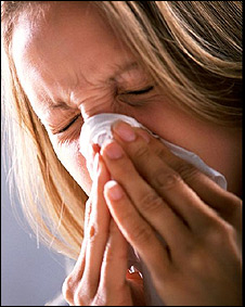 Una mujer limpiándose la nariz con un pañuelo