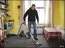 Un hombre pasando la aspiradora por una alfombra