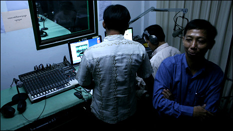 Cambodian radio staff look over an edit of a programme