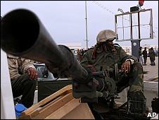 一名利比亚反卡扎菲武装在控制产油重镇拉斯拉努夫后坐在机枪旁放哨(5/3/2011)