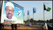 A woman walks past a billboard featuring presidential candidate of Congress for Progressive Change (CPC) Muhammadu Buhari in Kaduna Tuesday, March 1, 2011.
