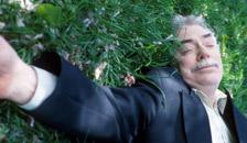 a man sleeping on a grassy lawn