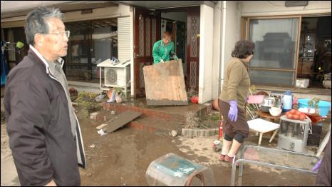 Família Hara em frente à casa tomada pelo mar de lama