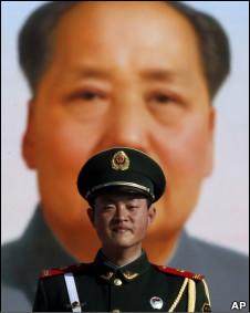 Policial chinês em frente a poster de Mao Tse Tung (Foto: AP)