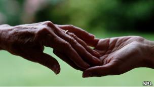 Manos de una persona anciana tocan las de una más joven