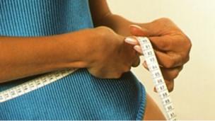 Mujer midiéndose la cintura