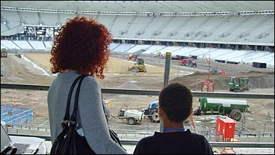 Hackney residents look at the London Olympic stadium being built
