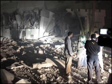 Watu wakizungumza karibu na jumba la Gaddafi la Babu al_aziziya baada ya kushambuliwa mwezi Aprili