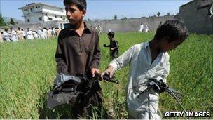 Niños paquistaníes con restos del helicóptero