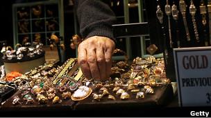 Un vendedor agarra una joya de oro