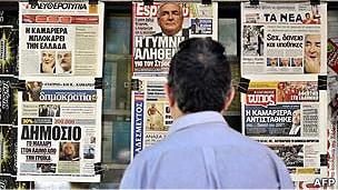 Hombre frente a diarios griegos