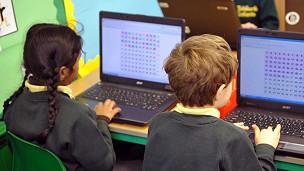 Dos niños utilizando computadoras.