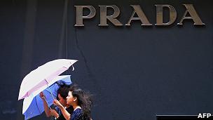 Jóvenes pasan frente a tienda de Prada en Hong Kong
