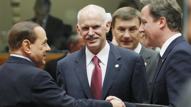 كاميرون (يمين) يصافح رئيس وزراء إيطاليا سليفيو بيرلسكوني (يسار) وباباندريو في الوسط