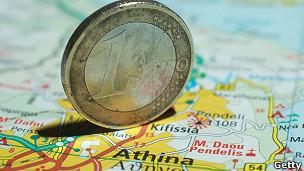 Moneda de un euro sobre mapa de Grecia