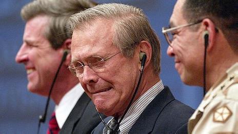 Donald Rumsfeld hace gestos al escuchar una traducción