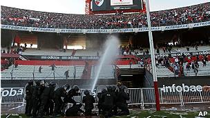 La policía lanza agua a presión contra la barra brava de River Plate para evitar que invadan el estadio.