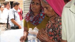 Mujeres compran comida con sus tarjetas inteligentes