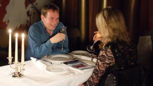 Pria dan wanita sedang makan malam di sebuah restoran