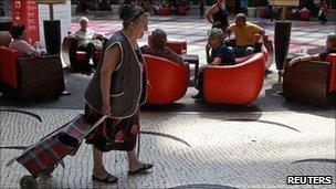 امراة تجر حقيبة للتسوق في أحد أسواق لشبونة