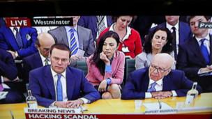 身穿粉红上衣的邓文迪在议会听证会上坐在默多克父子后面