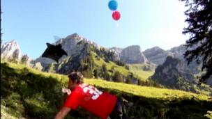 Jeb Corliss saltou de montanha de mais de 2 mil metros e tentou agarrar balões das mãos de pessoa que estava rente ao solo (BBC)