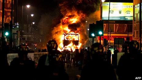 伦敦托特纳姆区骚乱现场一辆双层巴士在防暴警察面前焚烧(6/8/2011)
