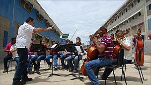 Prisioneiros ensaiam com a orquestra no pátio da penitenciária de Coro (BBC)