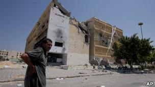 Homem em frente a edifício parcialmente destruído durante combates na parte central da cidade de Zawiya, na Líbia, no sábado, 20 de agosto de 2011