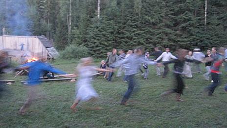 Gente bailando alrededor de una fogata en Estonia
