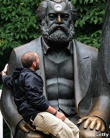 Chico sentado en las piernas de la estatua de Marx