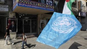 Bandeira da Palestina e da ONU diante de loja em Gaza, nesta quarta (AFP)