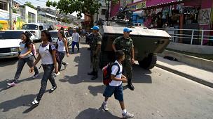 Estudantes passam por blindado no Complexo do Alemão. Foto: AFP