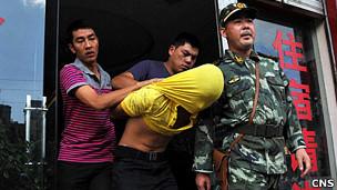 云南曲靖一名涉黑犯罪嫌疑人被便衣警察和武警拘捕(中新社图片21/8/2011)