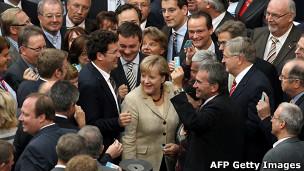 A chanceler alemã, Angela Merkel, visita o Parlamento europeu pouco antes de votação de medida que amplia poderes de fundo de resgate europeu