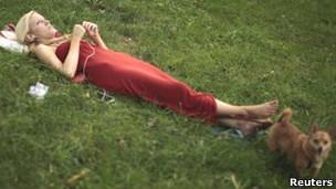 Mujer con iPod y perro en un parque