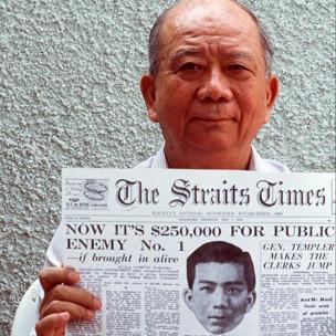 陈平展示《海峡时报》有关当局悬赏刺杀他的头版报道(资料图片)