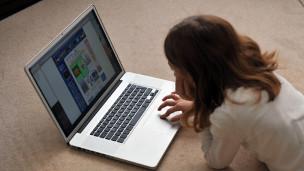 Una niña frente a un laptop