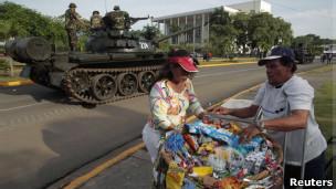Vendedor ambulante en frente de un tanque