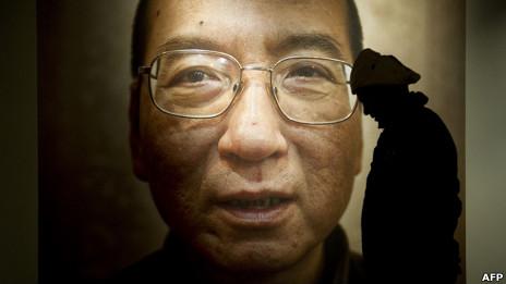 Một khách đi ngang qua ảnh của ông Lưu Hiểu Ba tại Trung tâm Hòa bình Oslo hồi năm 2010